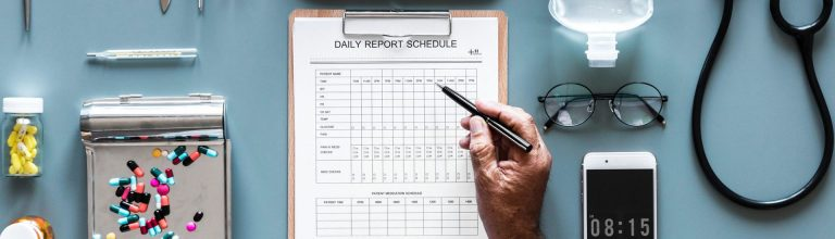 Doctors desk showing daily report schedule, pills, phone, and glasses